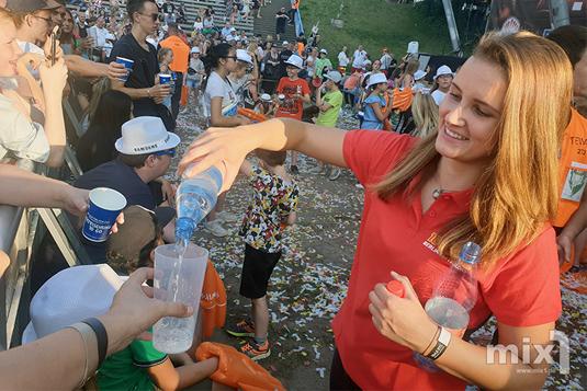 Hannah vom 104.6 RTL-Team versorgt bei 30 Grad die ersten Reihen mit Wasser